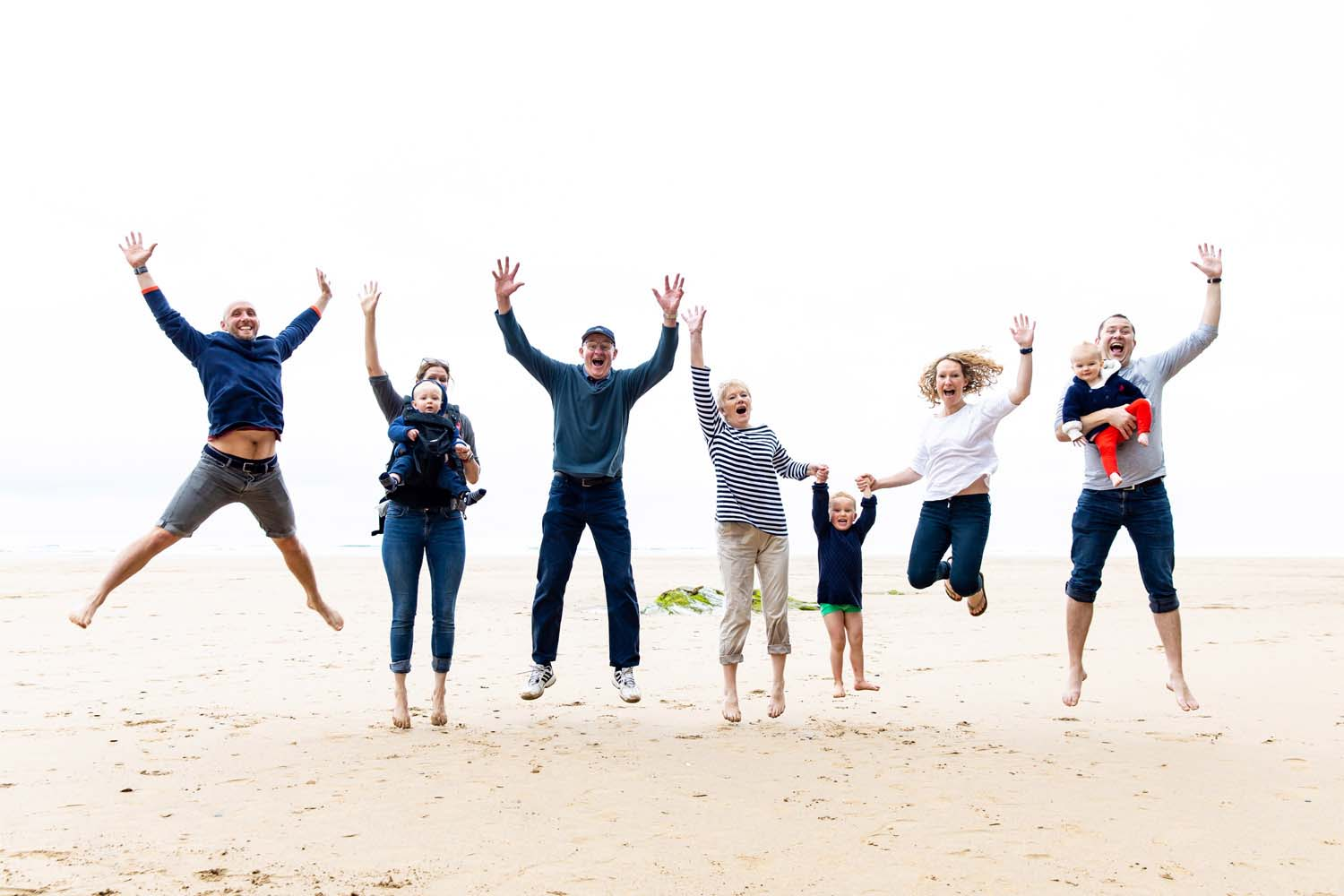 family jumping at Watergate beach Cornwall