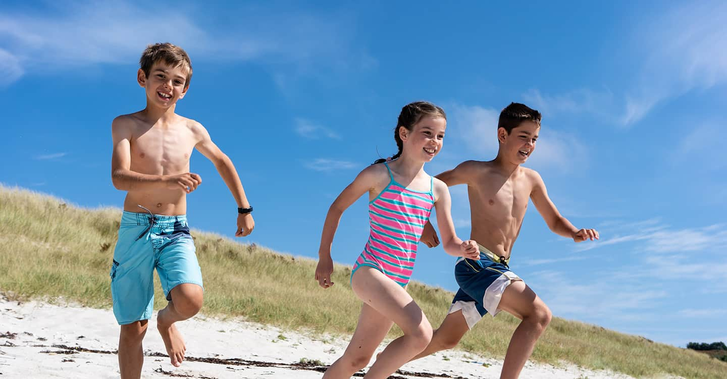 kids run on sandy beach